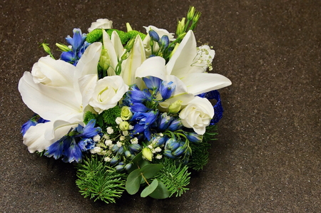 Christmas decoration with spruce branch, white lily, rose and blue bells on gray background