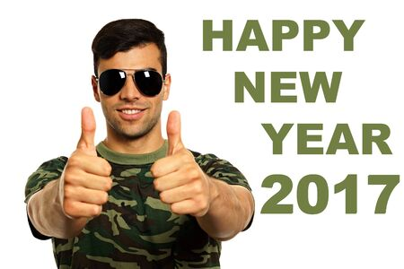 Happy new year 2017 with young smiling military man with a sunglasses shows you thumbs up