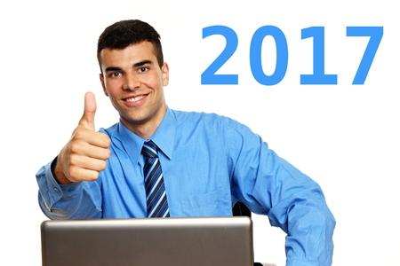 Frohes neues Jahr 2017 mit jungen Geschäftsmann im blauen Hemd zeigt Ihnen Daumen nach oben Standard-Bild - 69747071