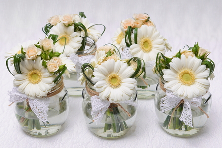 Beautiful wedding decoration with gerberas and roses on light background Standard-Bild
