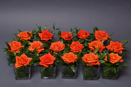 Beautiful decoration with orange roses in glasses on gray background 스톡 콘텐츠