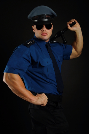 Policeman with sunglasses in uniform poses with police baton on dark background.