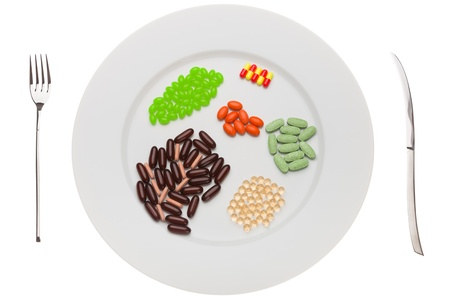 White plate with pills of  food supplements of different colors photo