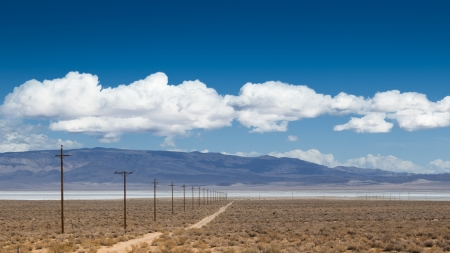 Dust road with power poles aside near salt Owens Lake in California, USA photo