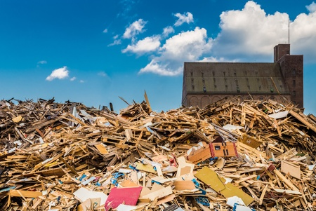 Pile of industrial wooden waste with old brick building and blue sky Stock Photo - 21646221