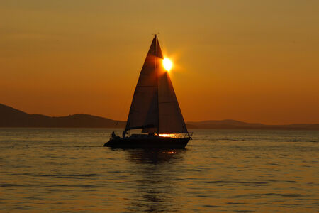 multi national: Sailing into the sunset with reflections on the sea surface Stock Photo