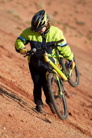 Girl on bike downhill in red canyon photo