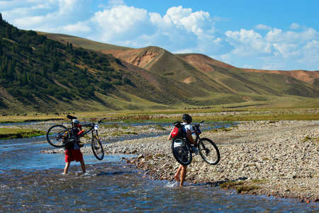 Two mountain bikers and mountain river Stock Photo