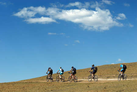 Mountain bikers on rural road and sky