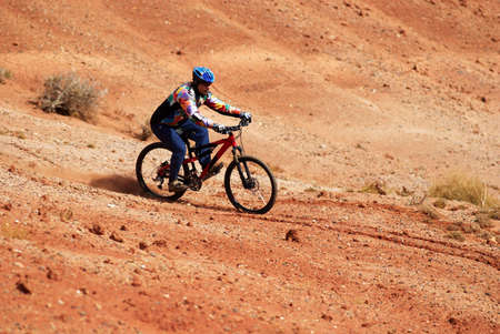 Biker on red loam hills photo
