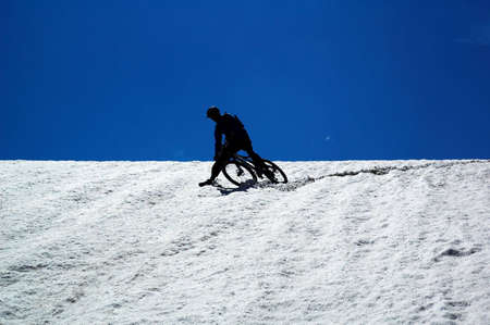 Sky, snow and mountain biker - downhill from mountain pass photo