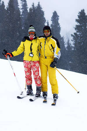 skiers: Yong family skiers in yellow and snowfall