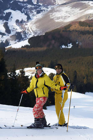 Yong family skiers in yellow on ski slope photo