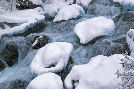 Winter mountain creek cascades during snowfall photo