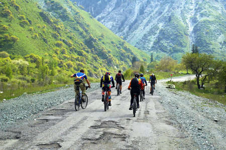 mountain bicycling: Group of the bikers on bad mountain road Stock Photo