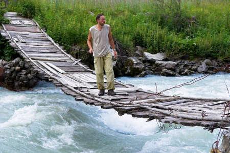 Man on old suspension bridge