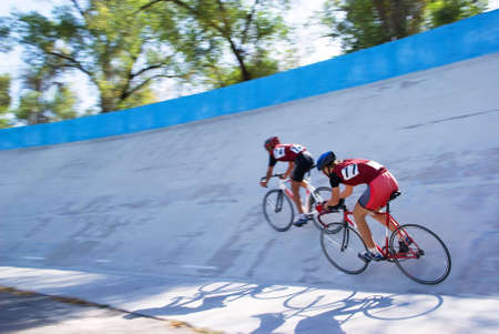 Two cyclist fast racing on velodrome