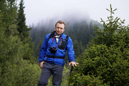 Backpacker man in mountain pine forest photo