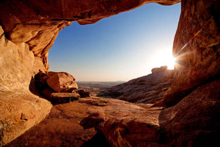 Entrance to cave and the sunset in desert mountains photo