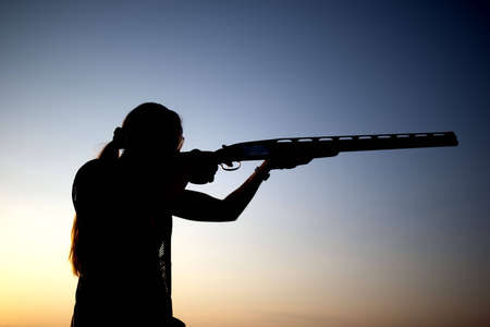 recreational: Woman shoots with his gun silhouette Stock Photo