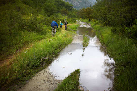 The group of bikers on the old mountain road in the rain photo