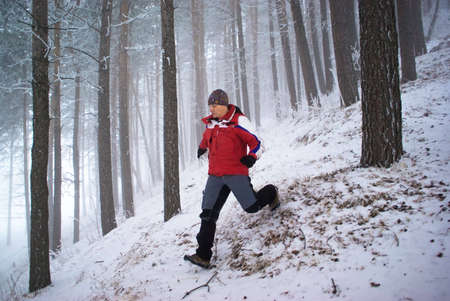 Blurred motion of running man in winter mountain forest photo
