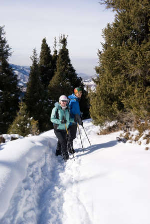 Smiling couple of backpackers in winter mountains photo
