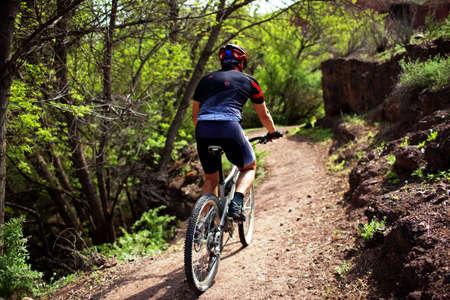 andando en bicicleta: Motociclista en camino en el bosque de monta�a