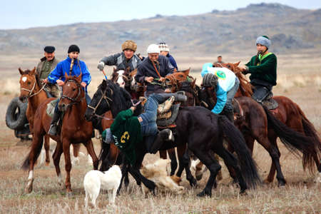 """UST-KAMENOGORSK, KAZAKHSTAN - OCTOBER 4 : A traditional nomad game of """"Kokpar"""" in action on October 4, 2009 in Ust-Kamenogorsk, Kazakhstan. Kokpar is played on horseback to carry dead goat carcass into a goal."""