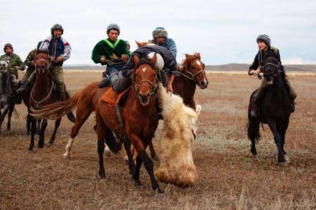 UST-KAMENOGORSK, Kazajstán-el 4 de octubre: Un juego de nómadas tradicionales de ?Kokpar? en acción el 4 de octubre de 2009 en Ust-Kamenogorsk, Kazajstán. Kokpar se juega a caballo a llevar el cadáver de cabra muerta en un gol.