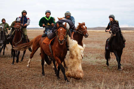 """UST-KAMENOGORSK, KAZAKHSTAN - OCTOBER 4 : A traditional nomad game of """"Kokpar"""" in action on October 4, 2009 in Ust-Kamenogorsk, Kazakhstan. Kokpar is played on horseback to carry dead goat carcass into a goal. Stock Photo - 7007174"""