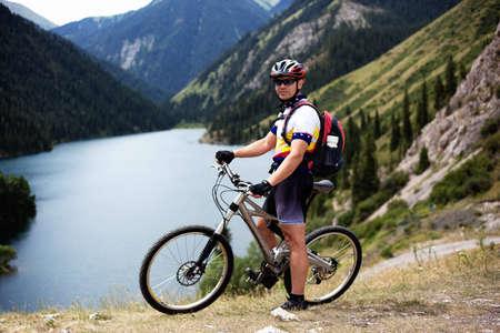 Cyclist beside a beautiful mountain lake photo