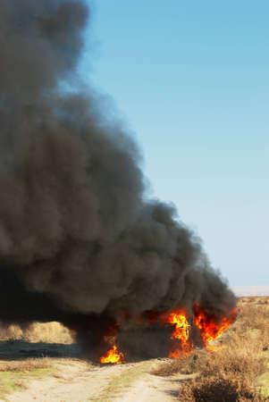 Car fire on desert rural road photo