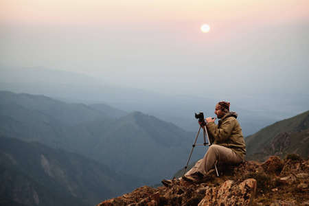 Photographer in the mountains at sunset