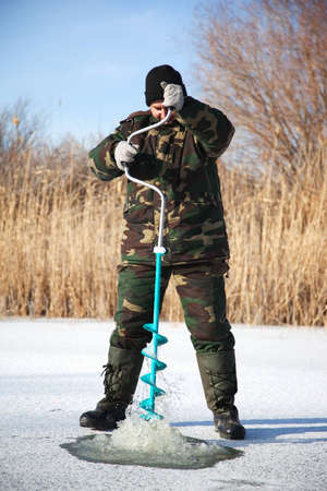 Ice fisherman drill on winter lake photo