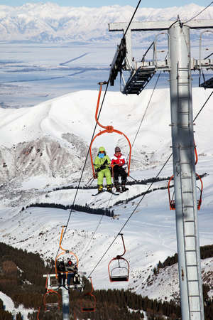 Couple on ski elevator in winter mountains photo