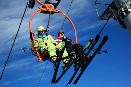 Couple on ski elevator in winter mountains Фото со стока