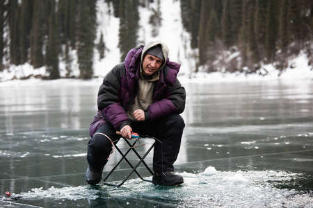 frozen lake: Ice fisherman on winter lake