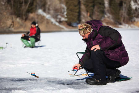 Ice fisherman on winter lake photo