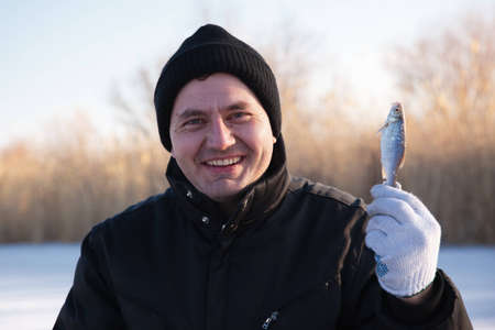 Ice fisherman with small fish photo
