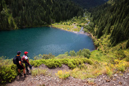 Two mans admiring the beauty of Kolsai lake, Kazakhstan photo