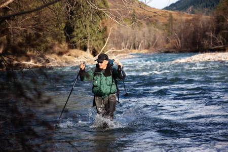 Backpacker wade rugged mountain river Stock Photo