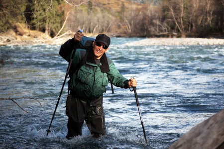 wade: Backpacker wade rugged mountain river Stock Photo