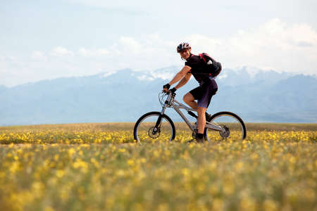 Smiling mountain biker and spring meadow photo