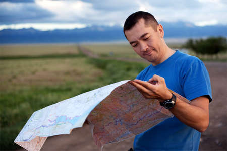 kazakhstan: Tourist exploring the map in the evening at sunset