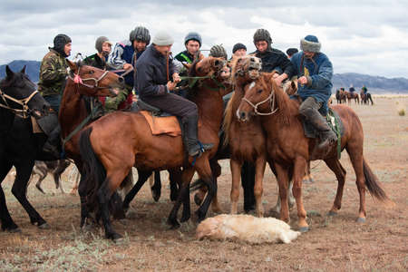 USTKAMAN, KAZAKHSTAN - OCTOBER 4 : A traditional nomad game of Kokpar in action on October 4, 2009 in Ustkaman, Kazakhstan. Kokpar is played on horseback to carry dead goat carcass into a goal. Editorial