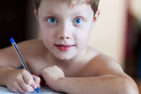 Boy doing his homework at home photo