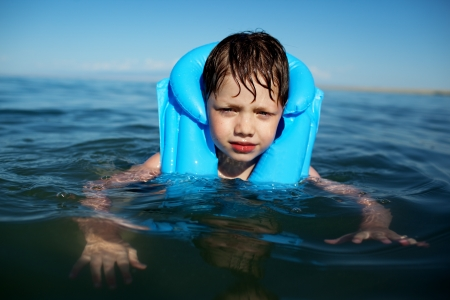 No smiling boy in the life-vest in the water Фото со стока