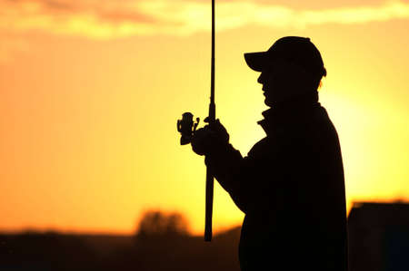 Fisherman silhouette at sunset photo