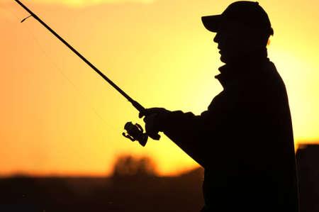 hombre pescando: Pescador silueta al atardecer Foto de archivo